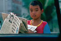 Boy sells newspapers at car windows in Manila, Philippines
