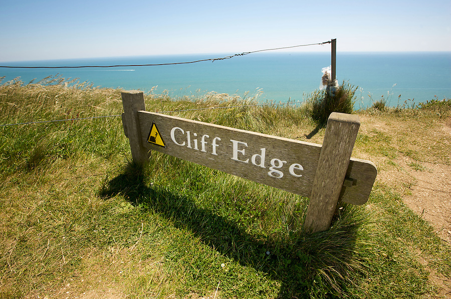 One of the UK's most famous landmarks the cliff face at Beachy Head on the South Downs is also notorious as a suicide spot. Warning signs and flower memorials are on the cliff edge.