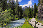 A view of the amazing peaks known as Sasso Lungo and Sasso Piatto as seen from the small town of Canazei, with the rapids of Rio d'Antermont in the foreground.