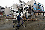 A man pushes his bicycle past a yacht that was forced into the side of a building by the force of the March 11 tsunami in Ishinomaki, Miyagi Prefecture, Japan on  15 March 20011..Photographer: Robert Gilhooly