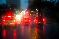 Commuters make the morning drive on Enfield Road during a rain storm in downtown Austin, Texas.