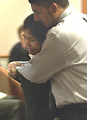 Margaret Walekar, wife of sniper victim Premkumar A. Walekar, is overcome as she leaves court in the arms of her son, Andrew, during the trial of sniper suspect John Allen Muhammad in courtroom 10 at the Virginia Beach Circuit Court in Virginia Beach, Virginia on October 27, 2003. Prosecution witnesses described the shooting of Walekar on October 3, 2002 at an Aspen Hill, Maryland gas station. <br /> Credit: Davis Turner - Pool via CNP
