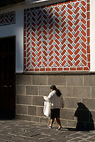 Woman walking beneath Talavera tiles on a building facade the city of Puebla, Mexico. The historical center of Puebla is a UNESCO World Heritage Site.