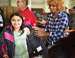 WATERBURY, CT- 27 November 2015-112715EC01--   Joselyn Rodriguez, 8, tries on a coat with the help of Shirelle Jones, a volunteer with St. Anne's Church along S. Main Street in Waterbury Friday. St. Anne's was one of six locations where Knights of Columbus distributed free coats for children. The Waterbury spot had nearly 500 coats to give away. 2,000 coats were distributed througout the state. Erin Covey Republican-American.