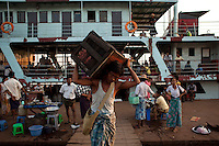 A labourer unloads a box from a passenger ferry at the Rangoon (Yangon) River docks.