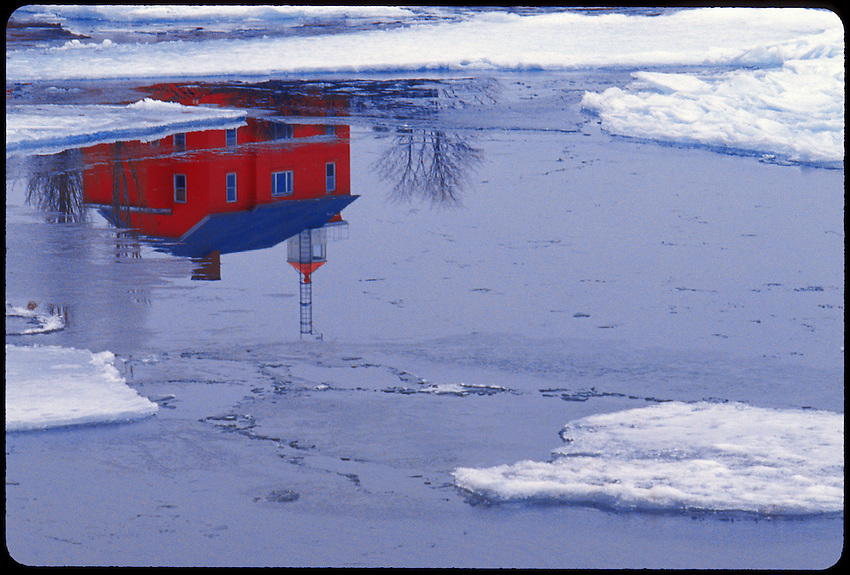 MARQUETTE LIGHTHOUSE RELECTION IN OPEN WATER BETWEEN ICE FLOES ON LAKE SUPERIOR IN WINTER IN MARQUETTE MICHIGAN.