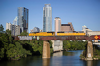 """Union Pacific Train passes over the """"Let's Pretend We're Robots,"""" a famous and beloved inspirational graffiti painting on a the railroad bridge over Lady Bird Lake, overlooking the Austin skyline."""