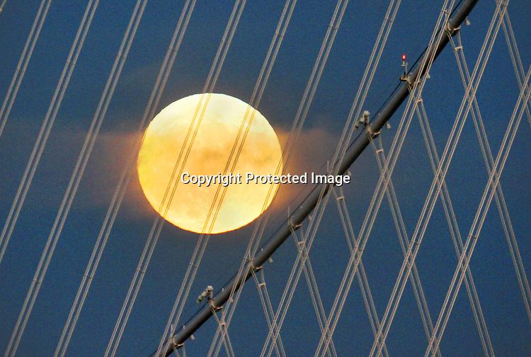 The November Supermoon over the Bay Bridge Tower seen from Treasure Island, CA.