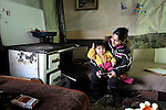Ivana Ibraimovic holds her 8-month old son Rasim inside their house in a Roma settlement in Belgrade, Serbia. The families that live here, many of whom survive from recycling cardboard and other materials, are under constant threat of eviction in order to make way for new high-rise office buildings. Ibraimovic heats her house by opening the oven door on the wood-fired stove behind her. Note: residents of this settlement were forcibly evicted in April 2012, two months after this photo. Many were relocated in metal shipping containers at the edge of the city.