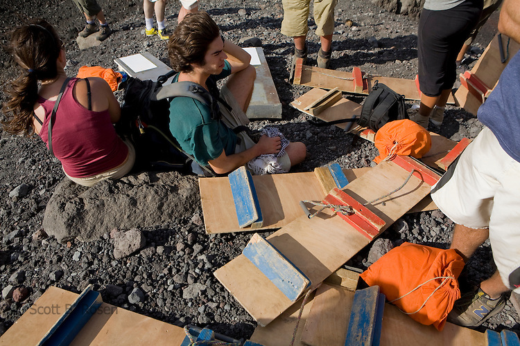 Backpackers rest with boards on route to the top of active Volcano Cerro Negro, Nicaragua