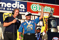Nov 13, 2016; Pomona, CA, USA; Fox Sports television announcer Bruno Massel (left) interviews NHRA funny car driver Ron Capps as he celebrates after clinching the championship during the Auto Club Finals at Auto Club Raceway at Pomona. Mandatory Credit: Mark J. Rebilas-USA TODAY Sports