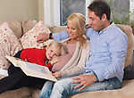Happy family watching photo album. Pregnant mother, daddy and their daughter expecting another baby.