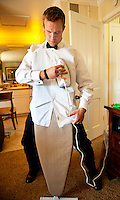 A groomsmen irons out a wrinkle not wanting to have to retie his bowtie before a wedding in Napa, CA.