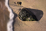 An intimate scene of the beach of Barcaggio at the northern tip of the Cap Corse in Corsica, France. Just a small rock lying in the sand and a tiny wave lapping on it. The scene somewhat reminds me of Zen gardens.
