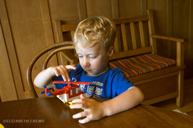 Berkeley CA Boy, four-years-old, fascinated with helicopter he's just constructed out of legos MR