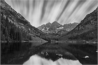 This image of the Maroon Bells, near Aspen, Colorado, was taken at night as a long exposure. The clouds were moving fast over the 5 minutes exposure, allowing the Maroon Bells and Maroon Lake and sky to light up under a nearly full moon.