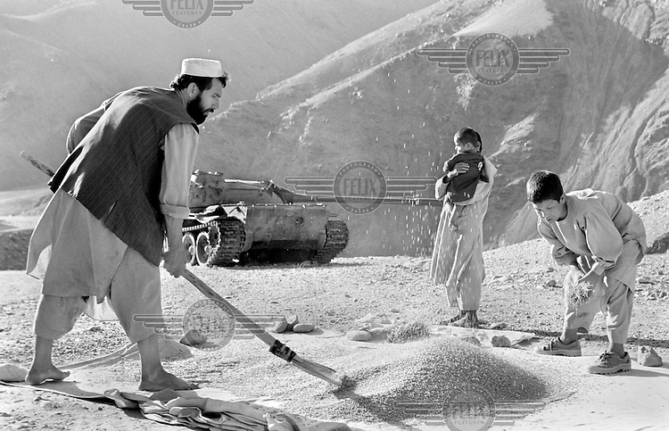 Recently returned from Iran, a farmer and some of his children work near Bamiyan, Aghanistan on June 25, 2002. A destroyed Soviet-built tank sits in the background. More than six million people fled Afghanistan during the years of conflict following the Soviet invasion in 1979.