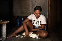 Indonesia - Bangka Island - Batako - Sumrya Rohmani, 38, from Madura Island petting her cat in the kitchen she shares with 5 more roomates. She has worked as a scrapper for 4 years. Before, she was working in a food-stall in Java. Her aunt invited her here, telling her she could get at least 5 USD per day. Her husband mines as well. She plans to stay in Bangka as long as there will be tin here.