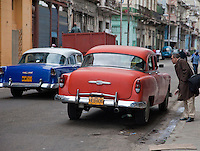 Cuba, Havana.  Early Morning Central Havana Street Scene.  Looking for a Taxi.  1950s Chevrolets.