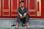 A woman sits for a portrait on the steps of the Mieu Temple inside the Citadel in the former imperial capital of Hue, Vietnam. April 21, 2013.