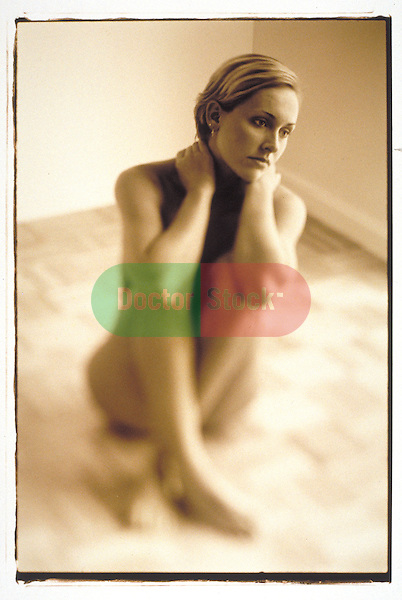 pensive nude woman sitting on floor in empty room, thinking