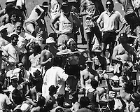 Female takes pulls her top up during a hot afternoon at a Oakland A's game at the Oakland Alameda County Coliseum..(July. 1988, photo by Ron Riesterer)