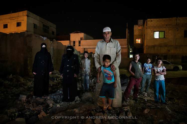 Fawaz Rarhail Turkey, 59, from Homs, Syria, pictured with his family outside a derelict house in Al Mafraq, Jordan, which they moved into after leaving Syria.<br /> <br /> &quot;The army forced entry into our homes and we became afraid for our children so we were forced to flee our country. We lived with Alawite people for 32 years but recently they changed their attitude toward us and attacked us. There were snipers everywhere, we saw them. Six months ago the army came into our house and they asked me if I was against the regime, they took me and my sons and accused us of being terrorists. 4 of my neighbours were killed by the Syrian soldiers, after that my brother was killed along with 8 people in the bathroom of a house.<br /> <br /> The first thing we did was to move to another area within Homs. One day we were attacked and all the families went to hide in the mosque, we stayed there for 2 hours and then a pick-up truck came and asked if we wanted to leave to a safer place, 20 of us went with him to Kara Shumshum then we moved to Biyda and to Khaldia, to Kassarah, to Haswieh, all within 1 week. At the end of the week we were in Hama. We stayed in Hama for 17 days and then we moved to Jordan. <br /> <br /> In Hama I met a man who had a micro-bus and he agreed to take 8 families to the border, 45 people in total. We traveled to Deraa and then the FSA (Free Syrian Army) helped us cross the border at night. We started walking at 8pm and arrived at 1am, at that time there were 150 people including elderly and children and we were afraid we would be targeted. There was co-ordination between the FSA and the Jordanians and the Jordanian army were waiting for us at the border. We were taken to a transit camp and treated well and then a Jordanian man came and agreed to be a guarantor for my family so we could stay in the country. After 3 days we came here to an abandoned house. We feel secure here and can sleep safely, not like in Syria. I was interviewed yesterday by an 