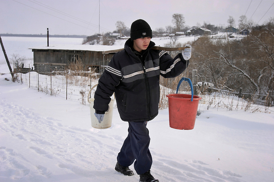 Sikachi-Alyan, Russia, 29/02/2004.&amp;#xD;Boy collecting drinking water from village well.<br />