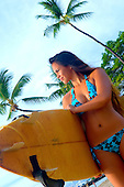 Young local girl with surf board and bikini near beach with palm trees