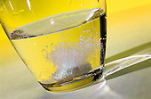 Tablet dissolving  in a glass of water.against a yellow background. Royalty Free