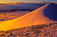 The setting sun casts a golden glow on the snow covered summit of Mauna Kea on the Big Island of Hawaii.