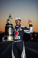 Nov 13, 2016; Pomona, CA, USA; NHRA top fuel driver Antron Brown celebrates as he poses for a portrait with the world championship trophy after clinching the championship during the Auto Club Finals at Auto Club Raceway at Pomona. Mandatory Credit: Mark J. Rebilas-USA TODAY Sports