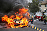 MANASQUAN, NJ — April 1, 2016 —Manasquan firefighter Kevin McCredie squirts water on a 2000 Ford Focus that is fully engulfed in flames about 9:40am on Broad Street, here. The driver of the vehicle, Nancy Trapani, was not injured.  photo by Andrew Mills