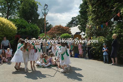Children dancing around a May Pole Petersham village fete Richmond Surrey UK.