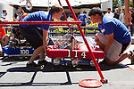 Nicholas Bousse and Mike Hua, left to right, remove their robot from a pyramid structure after competing in the first round of RoboNanza June 27.