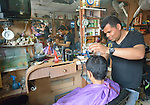 A boy gets his hair cut in a barber shop in the Zeitoun neighborhood of Gaza City, Gaza. Residents of the Palestinian territory are still reeling from the death and destruction of the 2014 war with Israel, and the continuing siege of the seaside territory by the Israeli military.