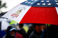 A fan uses their umbrella as the first stoppage in play occurs due to rain and thunderstorms during the 2016 U.S. Open in Oakmont, Pennsylvania on June 16, 2016. (Photo by Jared Wickerham / DKPS)