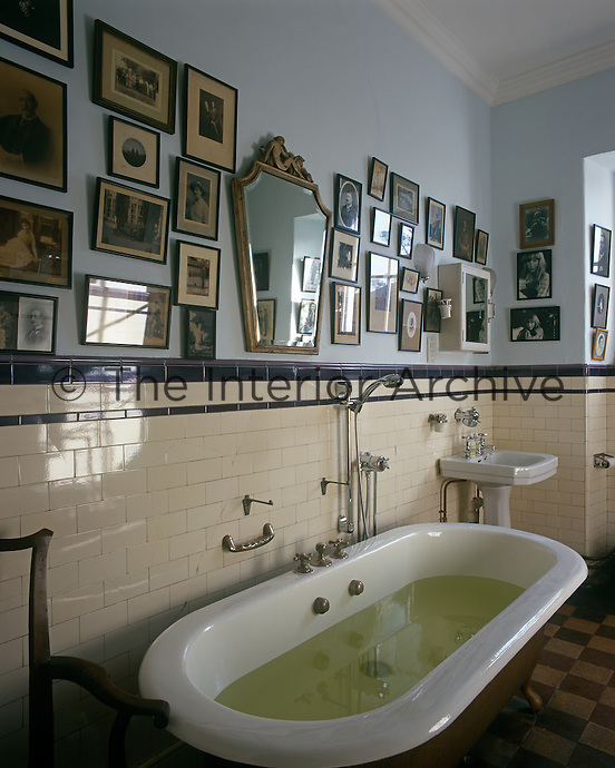 Metro tiles are teamed with a collection of old photographs in this traditional bathroom with a roll top bath