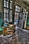Abandoned lunatic asylum north of Berlin, Germany. Cash till on desk with chair.