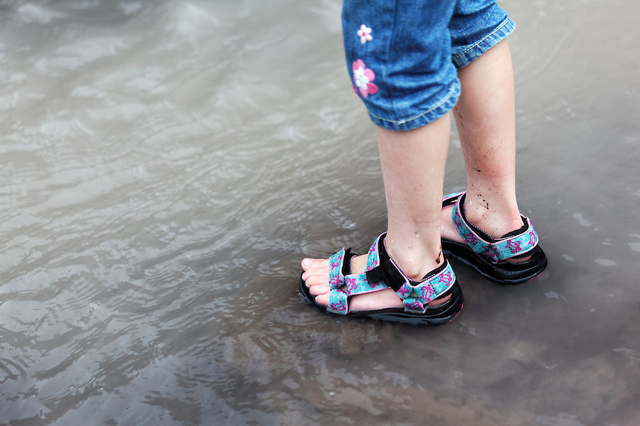 Feet of seven year old girl standing in Nisqually River, Mount Rainier National Park, Washington, USA, Pierce County