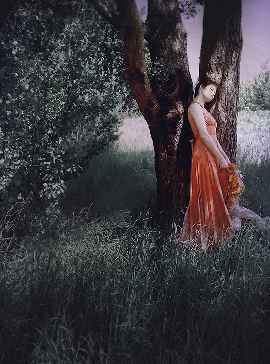 A woman in a red dress, holding a decorated hat, standing by a tree , sun setting in the background.