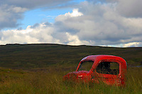 Old red painted car near Nordura river, near Borganes.