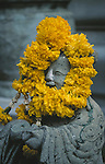 A concrete statue wears a garland of flowers in Wat Bowoniwet in the heart of Bangkok, Thailand.