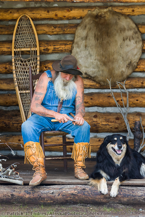 D. C. Smitty (Smitty) poses as a sourdough at his rustic log cabin, Glennallen, Alaska.