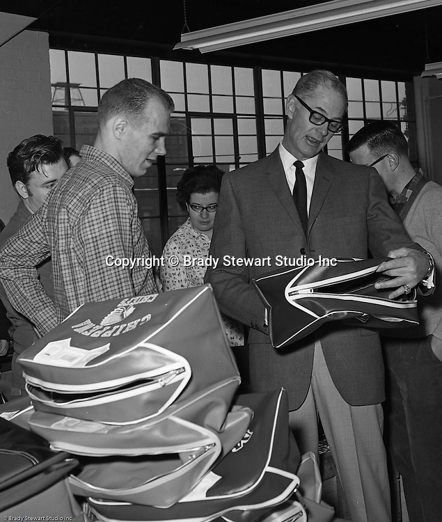 Pittsburgh PA:  Bob Prince touring the Goodwill Industries facility and talking with a few of the workers making gym bags for school districts - 1966.  <br /> In 1966, Goodwill Industries was part of the United Fund Community Chest Agency which eventually became the United Way of Allegheny County in 1974. Goodwill Industries provides a broad array of employment-related education and workforce development programs and services for people with physical and intellectual disabilities and other barriers to employment.
