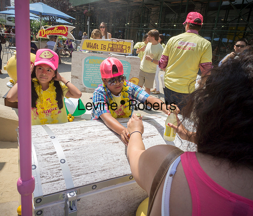 """Volunteers distribute bottles of lemonade for donations to 826NYC at """"Sweet and Sour Chillville"""" in Madison Square in New York on Wednesday, August 20, 2014. The 826NYC fundraising event is for the non-profit whose mission is to encourage students ages 8-18 in their writing skills and to promote teachers to inspire students to write. The organization is patterned after a similar one in California and promotes strong writing skills as a pathway to success.   (© Richard B. Levine)"""