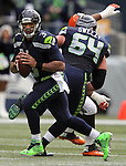 Seattle Seahawks quarterback Russell Wilson (3) scrambles against the Cleveland Browns Donte Whitner (31) and Karlos Danby (56)at CenturyLink Field in Seattle, Washington on December 20, 2015. The Seahawks clinched their fourth straight playoff berth in four seasons by beating the Browns 30-13.  ©2015. Jim Bryant Photo. All Rights Reserved.