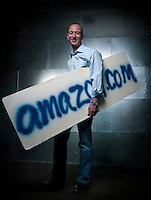 Jeff Bezos, founder of Amazon.com, holds the company's very first sign, quickly spray-painted prior to an interview with a Japanese television station in 1995, at their Seattle headquarters Thurs, May 11, 2004. (Photo by Andy Rogers)
