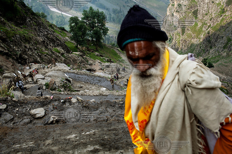 Hindu pilgrims walk along a mountain trail as they climb the Pissu Top pass (1500 feet, 3,400 metres) enroute to the Amarnath Cave. The pilgrims brave sub-zero temperatures and high altitude passes to reach the cave which houses a lingam, a stylised phallus, worshiped by Hindus as a symbol of the God Shiva.