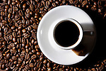 Stock photo of a Cup of black coffee on a saucer standing on coffee beans Artistic stil life